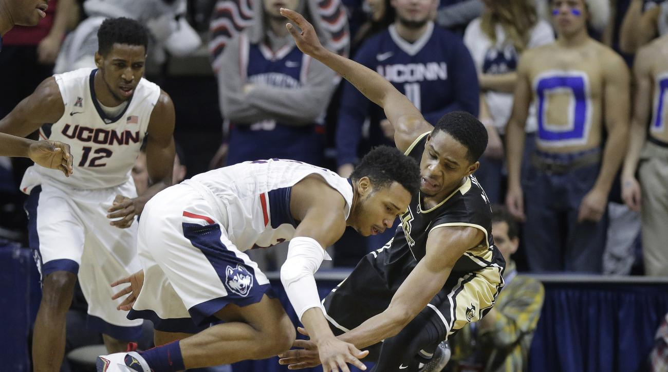 Connecticut's Jalen Adams, center, and Central Florida's A.J. Davis, right, chase a loose ball as Connecticut's Kentan Facey (12) looks on in the first half of an NCAA college basketball game Sunday, March 6, 2016, in Storrs, Conn. (AP Photo/Steven Senne)