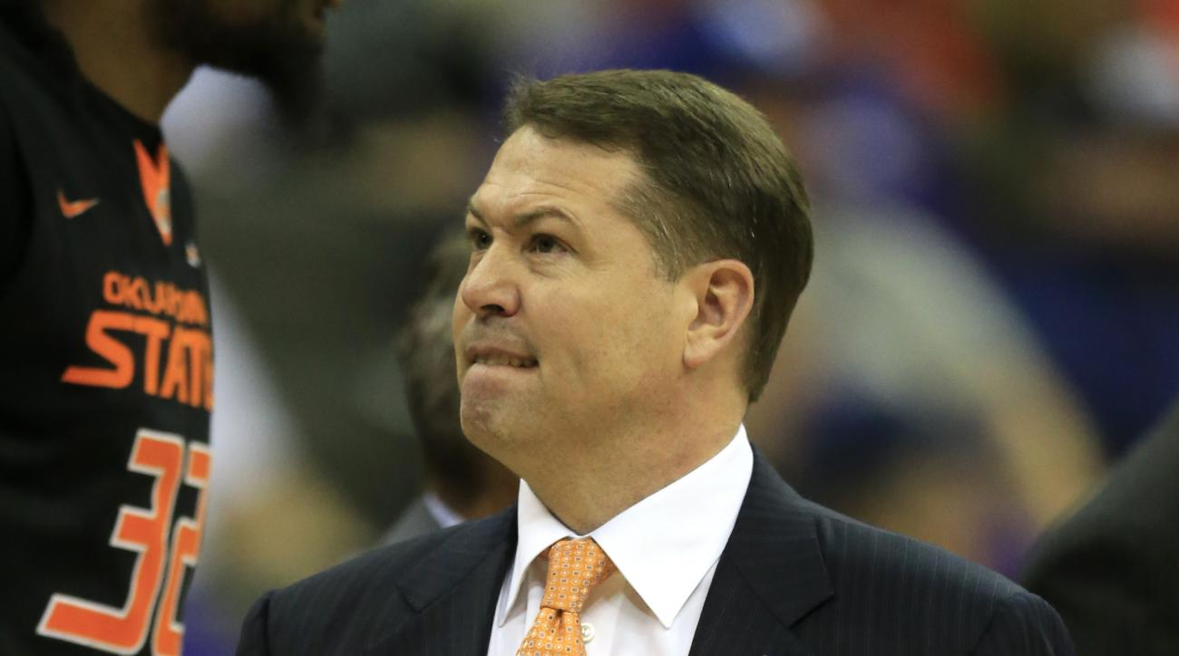 Oklahoma State head coach Travis Ford grimaces during the first half of an NCAA college basketball game against Kansas State in the first round of the Big 12 conference tournament in Kansas City, Mo., Wednesday, March 9, 2016. (AP Photo/Orlin Wagner)