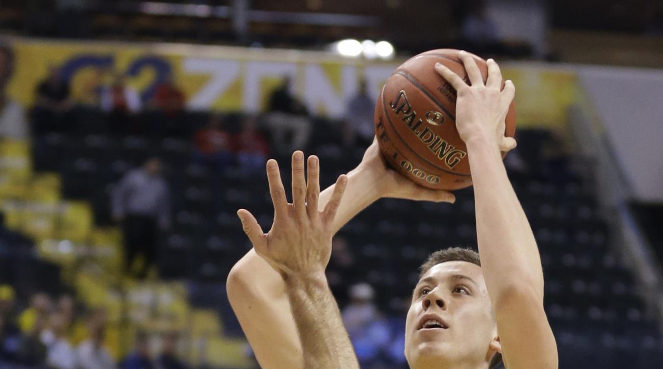 Michigan's Duncan Robinson (22) shoots against Northwestern's Tre Demps (14) in the first half of an NCAA college basketball game at the Big Ten Conference tournament, Thursday, March 10, 2016, in Indianapolis. (AP Photo/Michael Conroy)