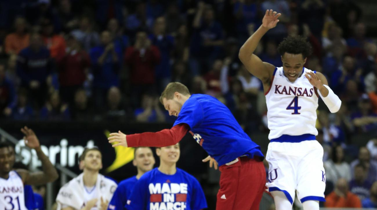 Kansas guards Devonte' Graham (4) and Tyler Self, left, celebrate at a timeout during the first half of an NCAA college basketball game against Kansas State in the quarterfinals of the Big 12 conference tournament in Kansas City, Mo., Thursday, March 10,