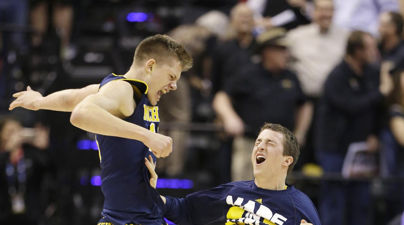 Michigan's Moritz Wagner, left, and Andrew Dakich celebrate after Kameron Chatman scored a game winning three point basket in the second half of an NCAA college basketball game against the Indiana in the quarterfinals at the Big Ten Conference tournament,