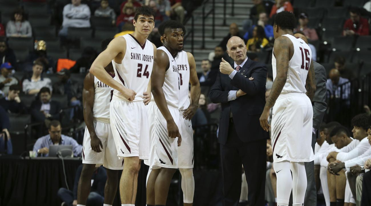 Saint Joseph head coach Phil Martelli talks to his players during a time out in the first half of an NCAA college basketball game against George Washington in the Atlantic 10 men's tournament, Friday, March 11, 2016, at New York. (AP Photo/Mary Altaffer)