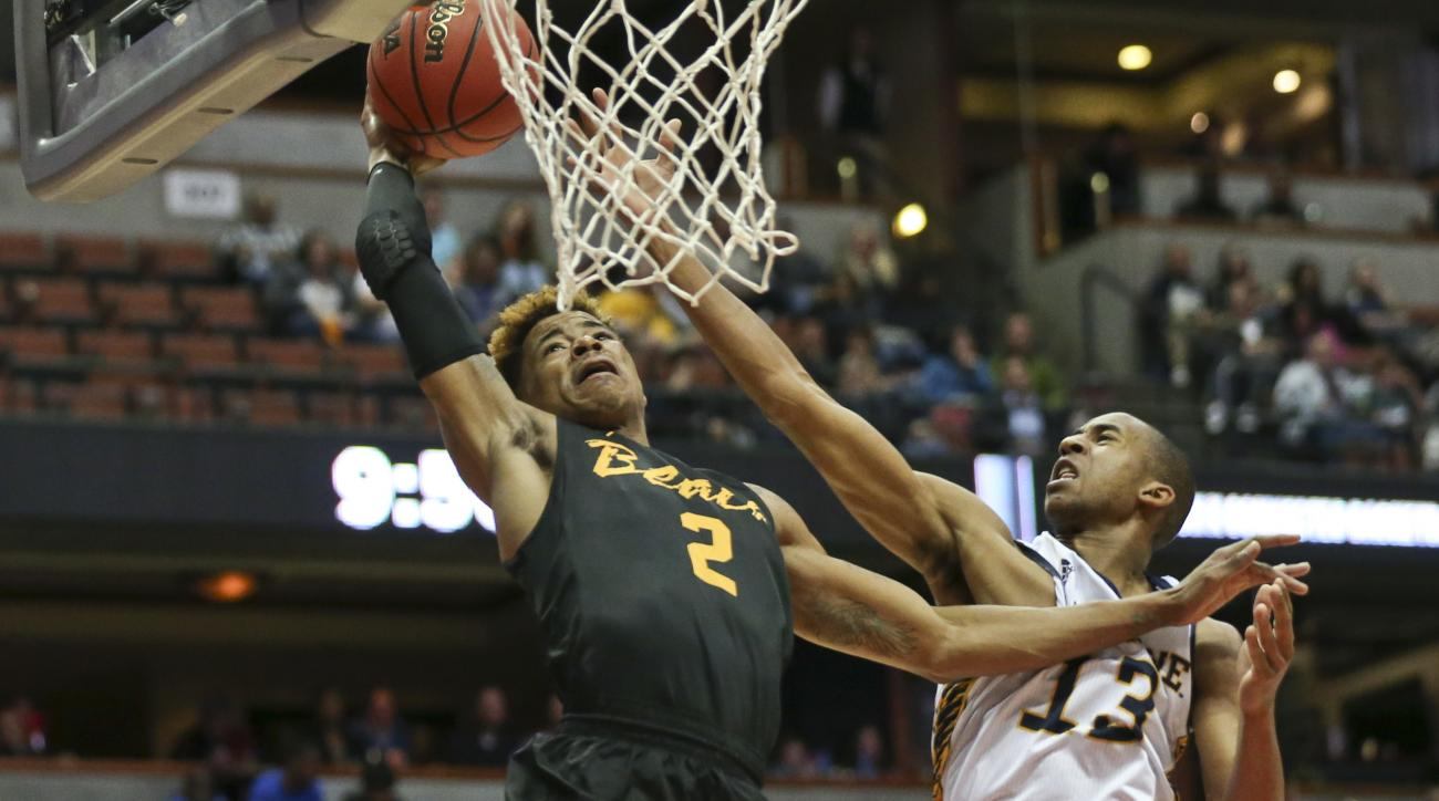 Long Beach State's Nick Faust takes a pass before dunking against UC Irvine's Branford Jones during the first half of an NCAA college basketball game at the Big West conference men's tournament Friday, March 11, 2016, in Anaheim, Calif. (AP Photo/Lenny Ig