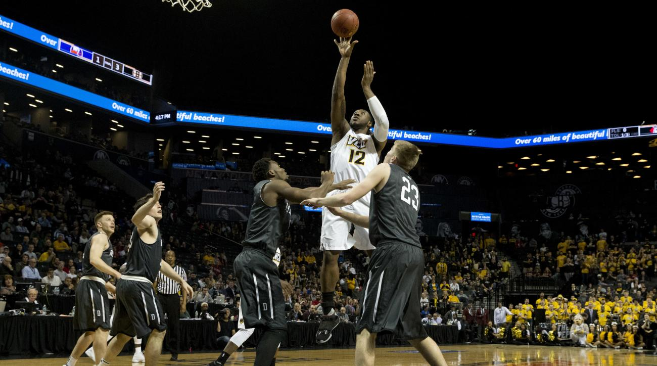 Virginia Commonwealth forward Mo Alie-Cox (12) goes to the basket against Davidson forward Peyton Aldridge and forward Nathan Ekwu (1) during the first half of an NCAA college basketball game during the semifinals of the Atlantic 10 men's tournament, Satu