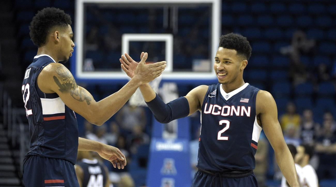 Connecticut guard Jalen Adams (2) and forward Shonn Miller (32) celebrate after a score at the end of the second half of an NCAA college basketball game against Temple in the semifinals of the American Athletic Conference men's tournament in Orlando, Fla.