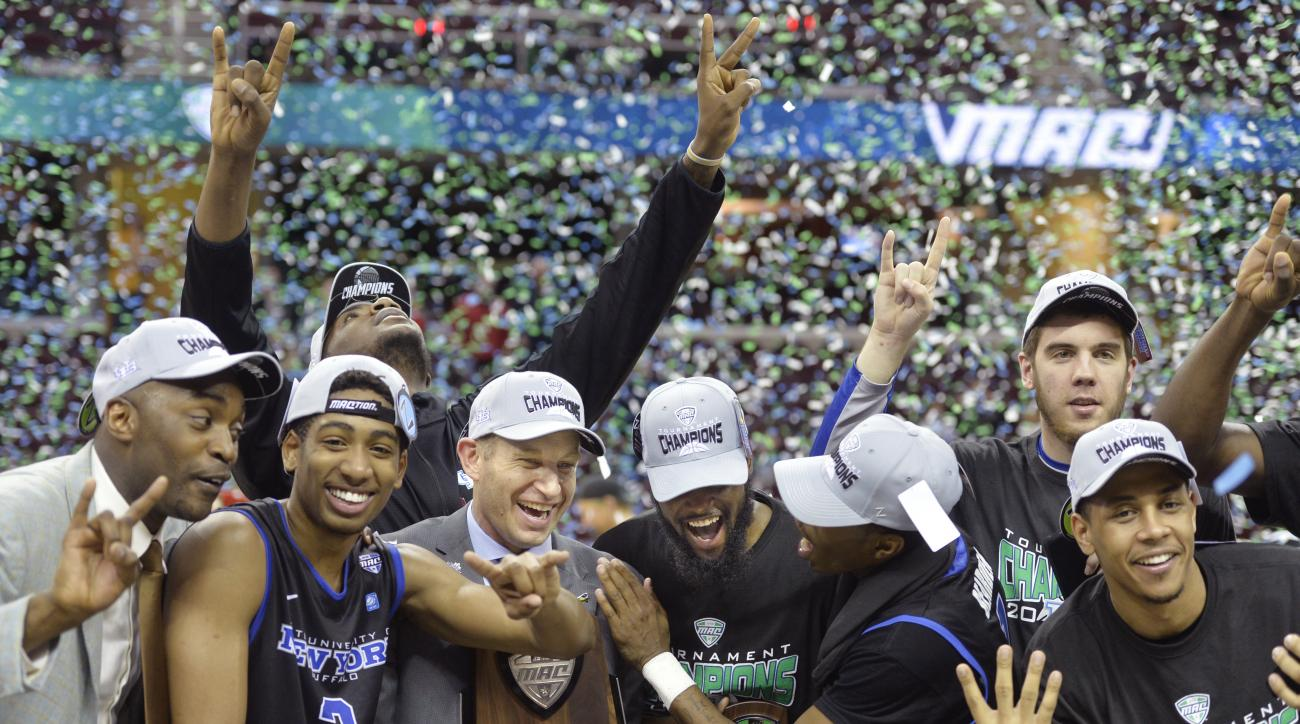 Buffalo head coach Nate Oats holds the championship trophy while celebrating with his team after a win over Akron in an NCAA college basketball game in the championship of the Mid-American Conference men's tournament, Saturday, March 12, 2016, in Clevelan
