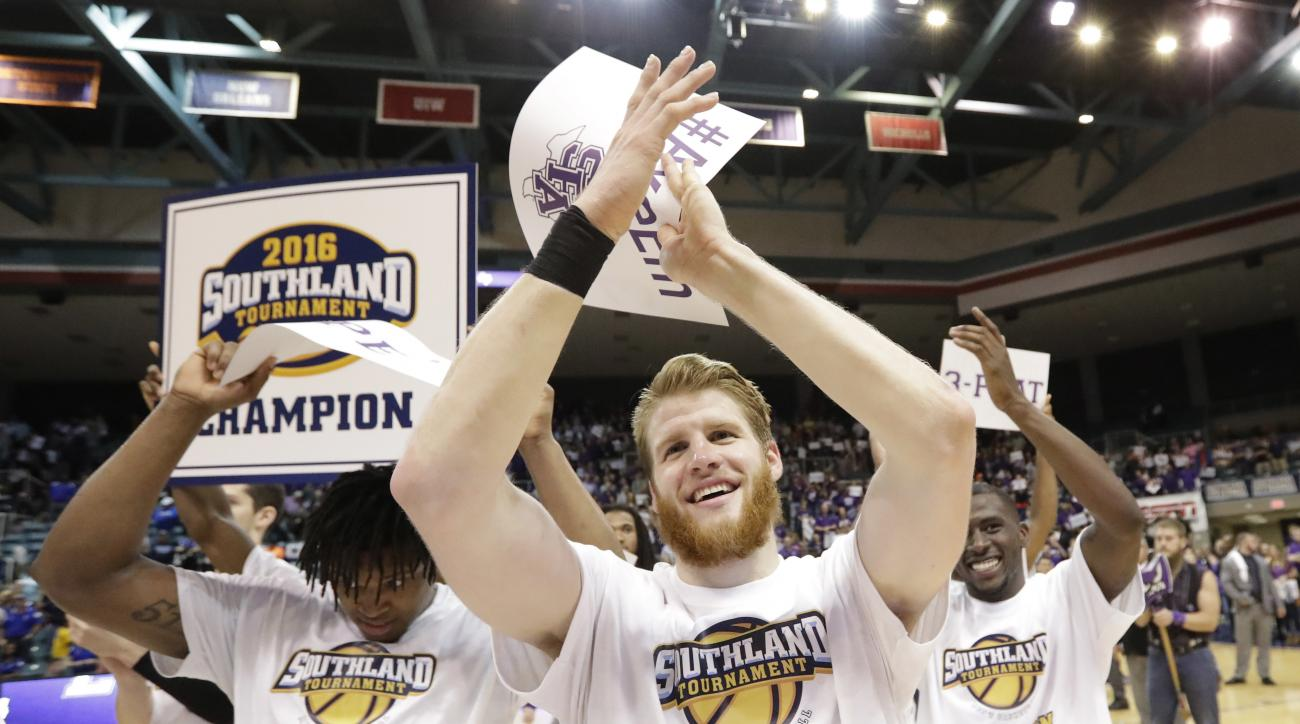 Stephen F. Austin's Thomas Walkup, center, celebrates with teammates after an NCAA college basketball game against Texas A&M-Corpus Christi in the championship of the Southland Conference men's tournament, Saturday, March 12, 2016, in Katy, Texas. Stephen