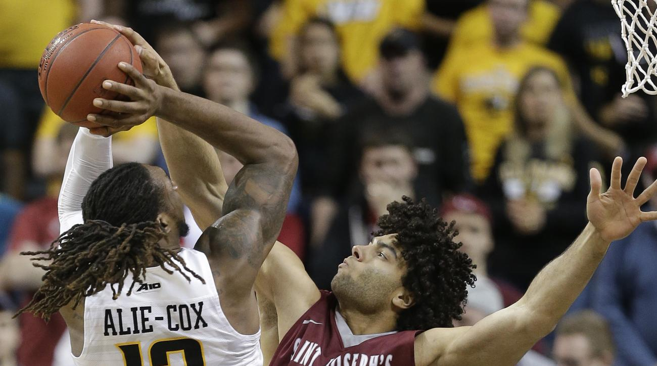 Saint Joseph's forward Javon Baumann (34) blocks a shot by Virginia Commonwealth forward Mo Alie-Cox (12) in the second half of an NCAA college basketball game during the championship game of the Atlantic 10 men's tournament, Sunday, March 13, 2016, in Ne