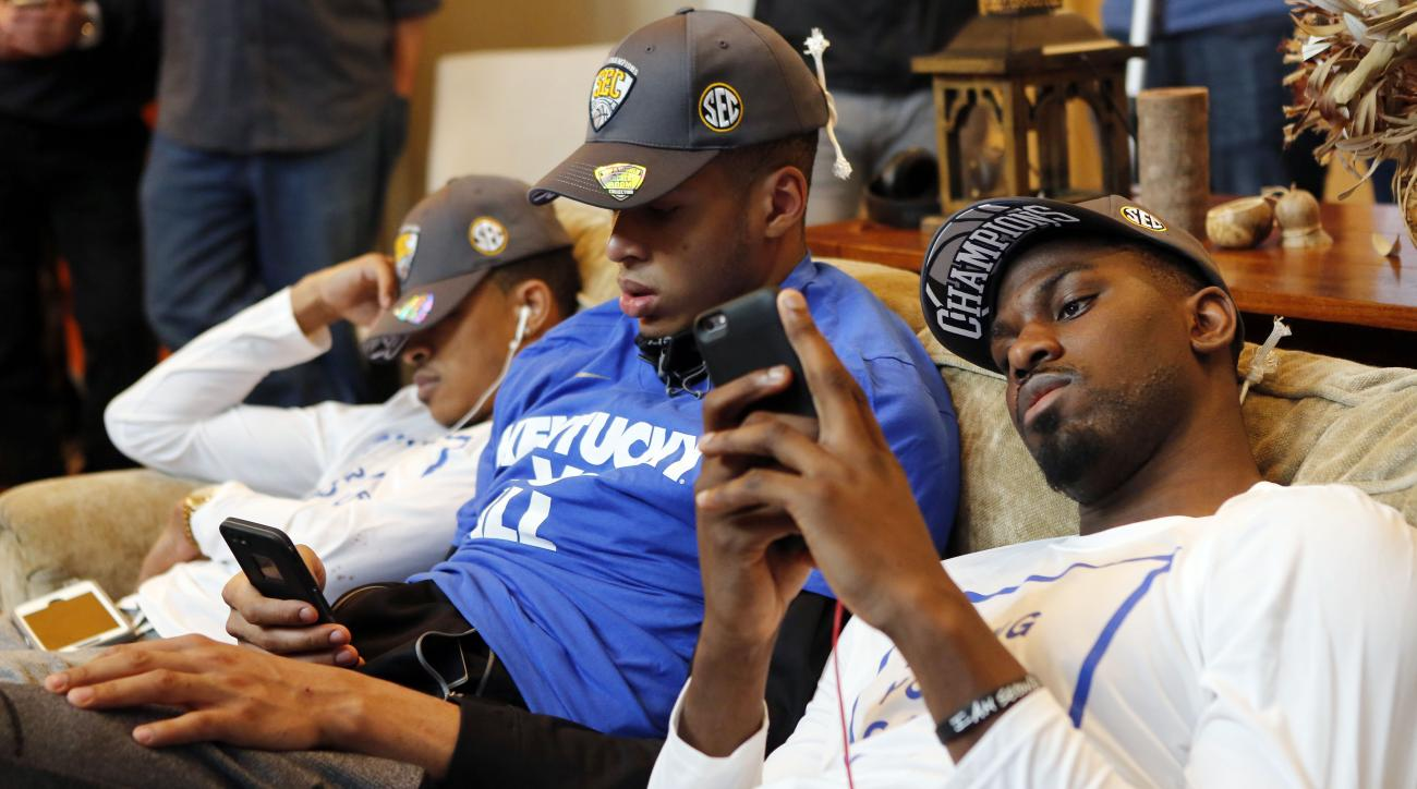 From left, Kentucky's Tyler Ulis sleeps while Skal Labissiere and Alex Poythress check their phones as other members of the men's college basketball team watch the NCAA tournament selection show at the home of head coach John Calipari on Sunday, March 13,
