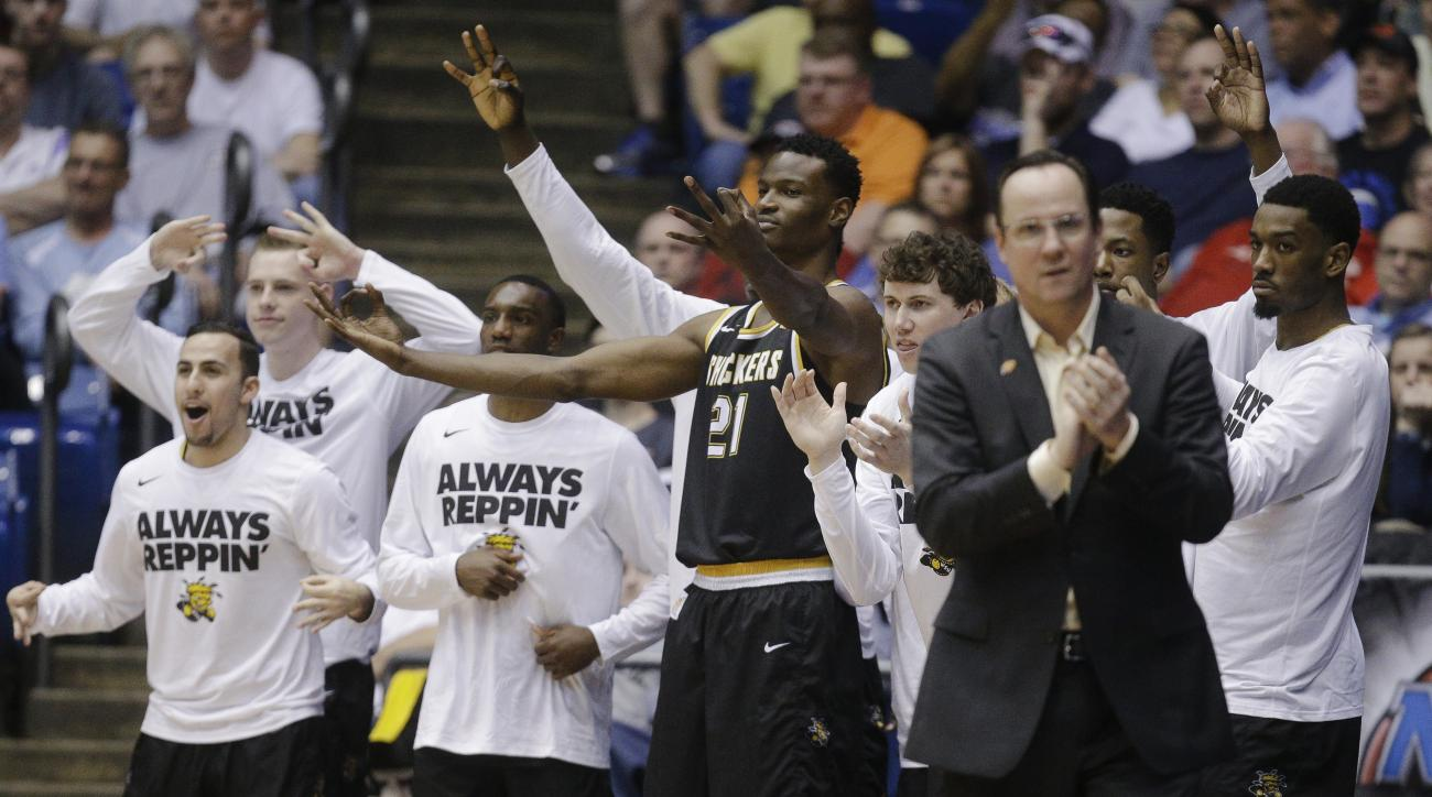 Wichita State's Bush Wamukota (21) and the Wichita State bench react during the second half of a First Four game of the NCAA men's college basketball tournament against Vanderbilt, Tuesday, March 15, 2016, in Dayton, Ohio. Wichita State won 70-50. (AP Pho