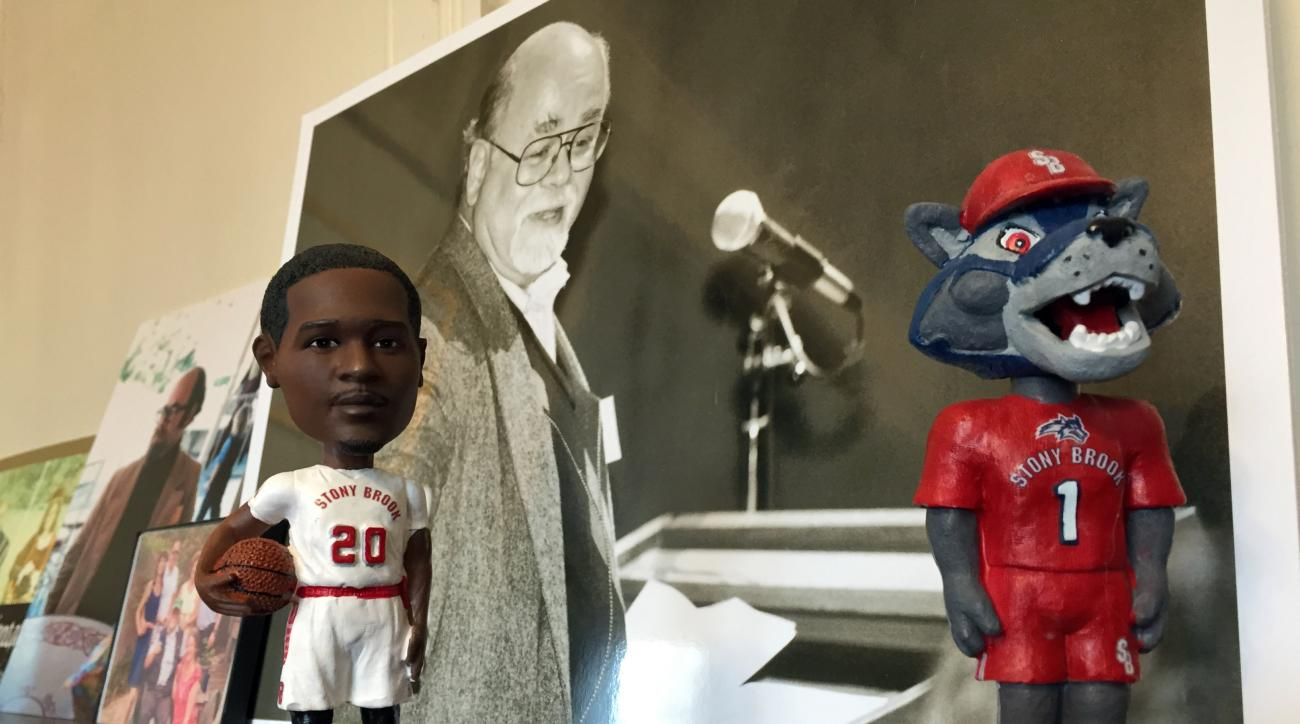 In this photo taken Tuesday, March 15, 2016, bobbleheads of Stony Brook basketball star Jameel Warney and the school mascot, Wolfie, frame of photo of Richard Solo at the family's home in Port Jefferson, N.Y. Solo, a longtime Stony Brook professor, admini
