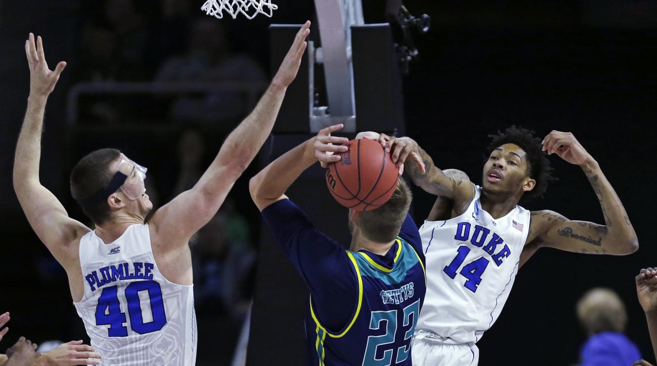Duke guard Brandon Ingram (14) and center Marshall Plumlee (40) double team North Carolina-Wilmington center C.J. Gettys (23) and block his drive to the basket in the first half during the first round of the NCAA college men's basketball tournament in Pro
