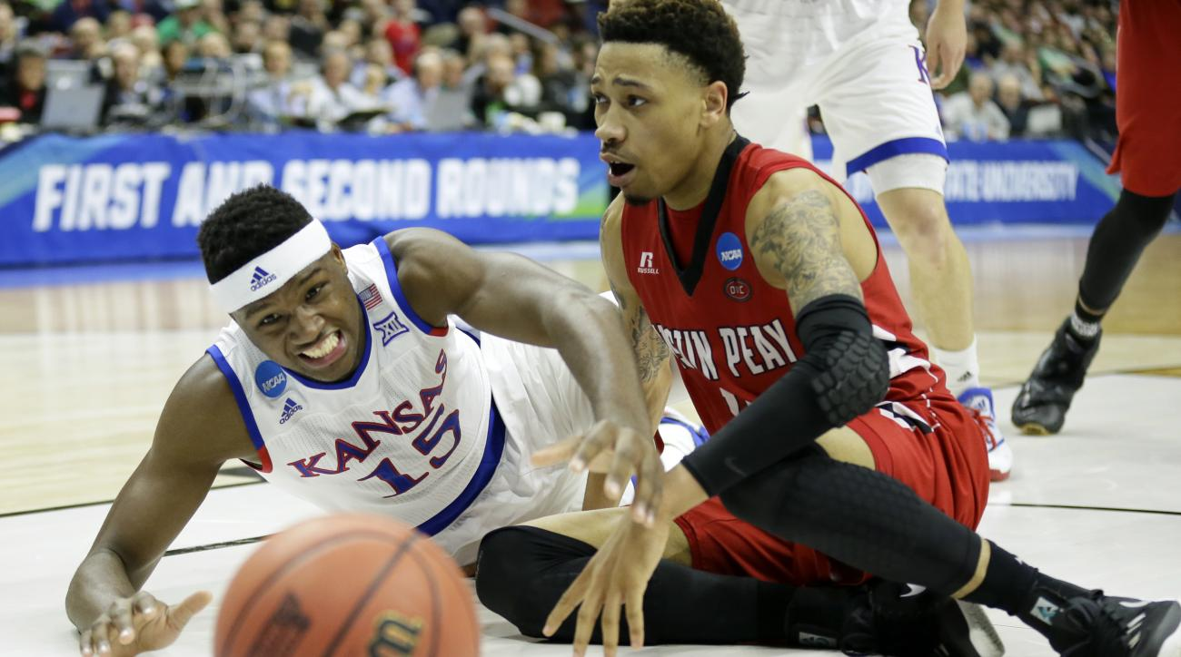Kansas forward Carlton Bragg Jr., left, fights for the ball with Austin Peay guard Khalil Davis during the first half of a first-round men's college basketball game in the NCAA Tournament, Thursday, March 17, 2016, in Des Moines, Iowa. (AP Photo/Charlie N