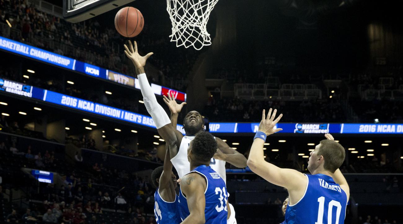 Villanova forward Daniel Ochefu, center, goes to the basket against UNC Asheville forward Sam Hughes (31) and guard Kevin Vannatta (10) during the first half of a first-round men's college basketball game in the NCAA Tournament, Friday, March 18, 2016, in