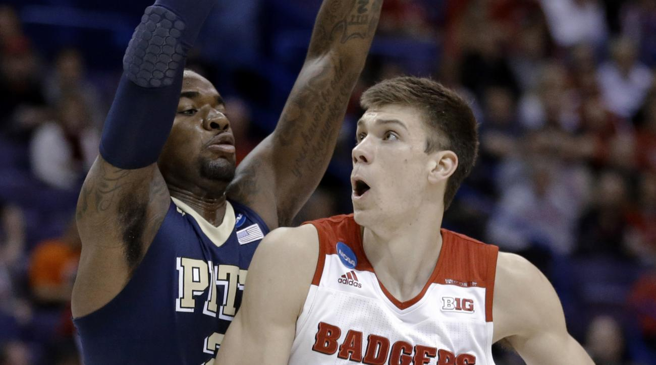 Wisconsin's Ethan Happ, right, looks to the basket as Pittsburgh's Michael Young defends during the first half in a first-round men's college basketball game in the NCAA tournament, Friday, March 18, 2016, in St. Louis. (AP Photo/Jeff Roberson)