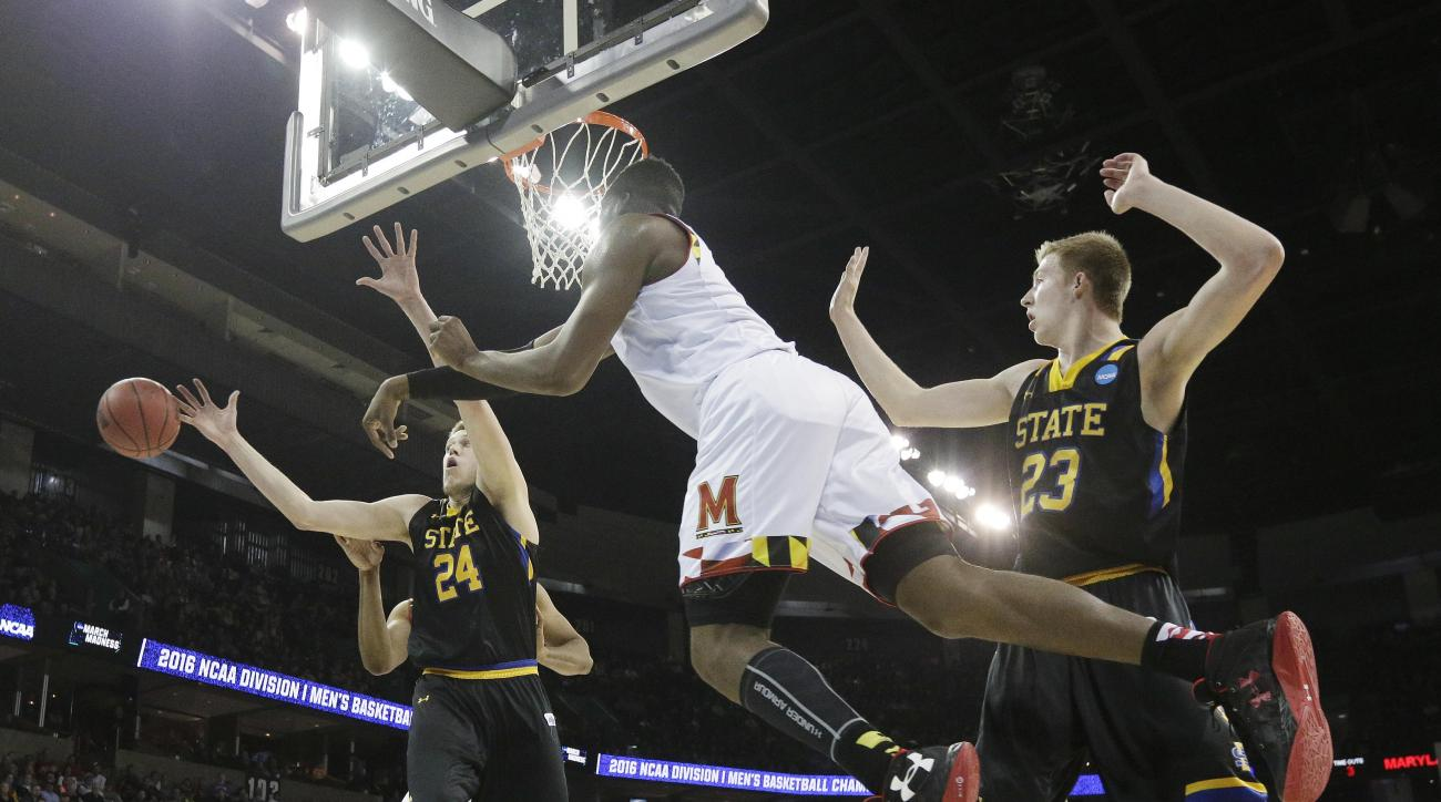 Maryland forward Robert Carter, center, passes the ball around South Dakota State forward Mike Daum (24) and forward Logan Doyle (33) during the second half of a first-round men's college basketball game in the NCAA Tournament in Spokane, Wash., Friday, M