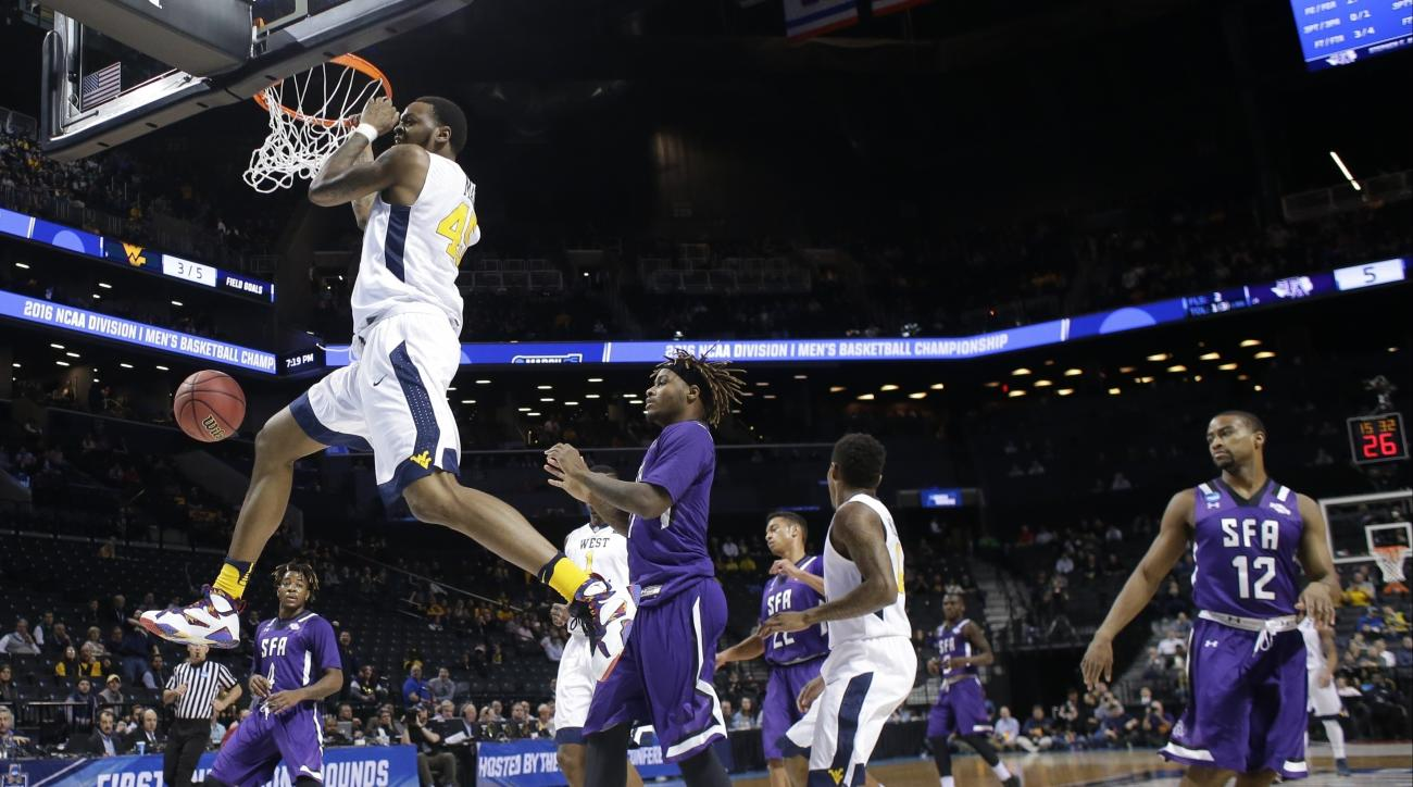 West Virginia's Elijah Macon (45) dunks the ball in front Stephen F. Austin's Clide Geffrard, Jr. (11) during the first half of a first-round men's college basketball game in the NCAA Tournament,Friday, March 18, 2016, in New York. (AP Photo/Frank Frankli