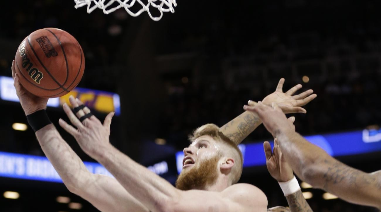 Stephen F. Austin's Thomas Walkup (0) drives past West Virginia's Elijah Macon (45) during the second half of a first-round men's college basketball game in the NCAA Tournament,Friday, March 18, 2016, in New York. (AP Photo/Frank Franklin II)