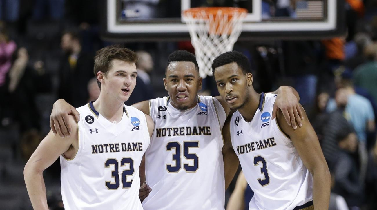 Notre Dame's Steve Vasturia (32), Bonzie Colson (35) and V.J. Beachem (3) talk during the second half of a first-round men's college basketball game against Michigan in the NCAA Tournament, Friday, March 18, 2016, in New York. Notre Dame won 70-63. (AP Ph