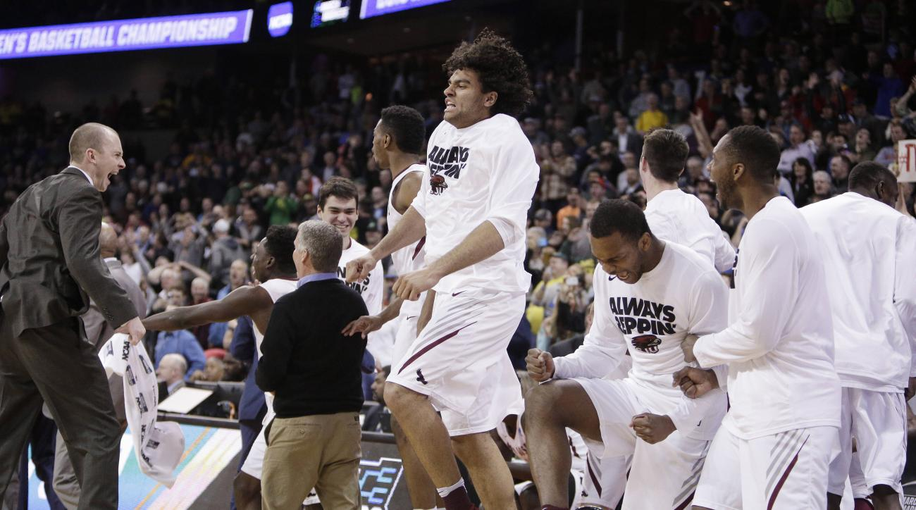 Saint Joseph's players and coaches celebrate after winning a first-round men's college basketball game in the NCAA Tournament against Cincinnati in Spokane, Wash., Friday, March 18, 2016. Saint Joseph's won 78-76. (AP Photo/Young Kwak)