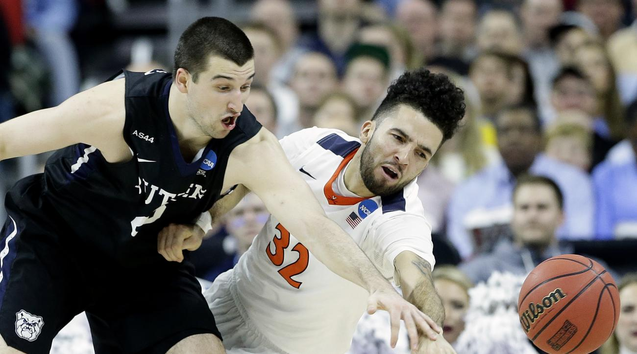 Virginia guard London Perrantes (32) and Butler forward Andrew Chrabascz (45) chase a loose ball during the second half of a second-round men's college basketball game in the NCAA Tournament, Saturday, March 19, 2016, in Raleigh, N.C. (AP Photo/Gerry Broo