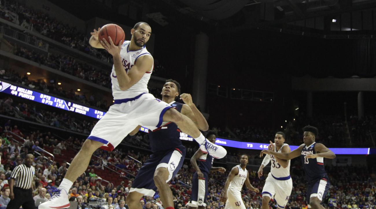 Kansas forward Perry Ellis, left, grabs a rebound over Connecticut forward Shonn Miller during the first half of a second-round men's college basketball game in the NCAA Tournament, Saturday, March 19, 2016, in Des Moines, Iowa. (AP Photo/Charlie Neiberga