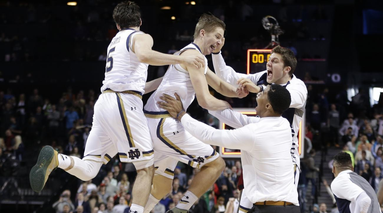 Notre Dame's Rex Pflueger, center, and Matt Farrell, left, celebrate with teammates after a second-round men's college basketball game in the NCAA Tournament, Sunday, March 20, 2016, in New York. Notre Dame won 76-75. (AP Photo/Frank Franklin II)