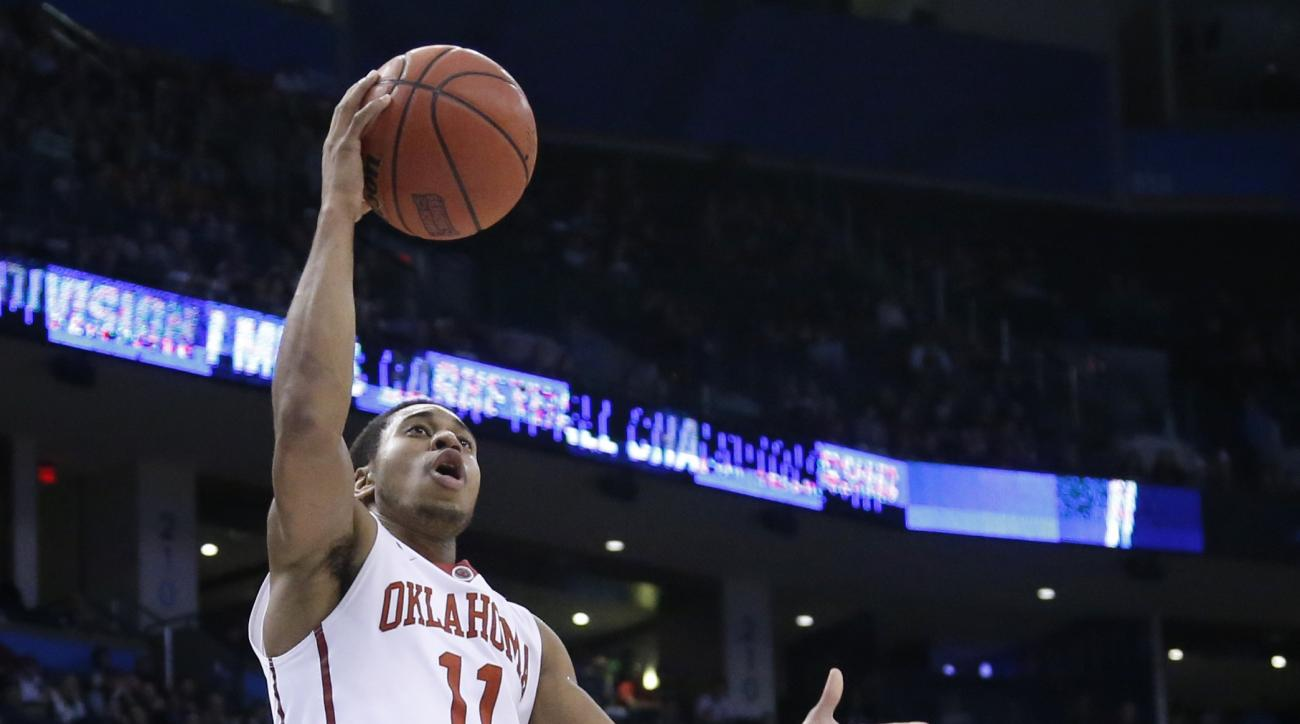 Oklahoma guard Isaiah Cousins (11) shoots in front of Virginia Commonwealth guard Jonathan Williams (10) in the first half of a second-round men's college basketball game in the NCAA Tournament Sunday, March 20, 2016, in Oklahoma City.  (AP Photo/Sue Ogro