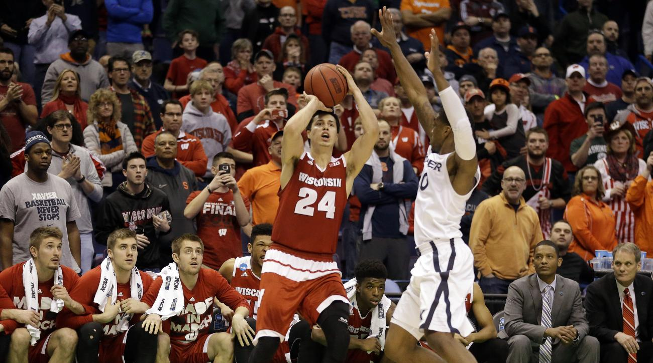 Wisconsin's Bronson Koenig (24) shoots a last second 3-point shot over Xavier's Remy Abell to give Wisconsin a 66-63 victory in a second-round men's college basketball game in the NCAA Tournament, Sunday, March 20, 2016, in St. Louis. (AP Photo/Jeff Rober