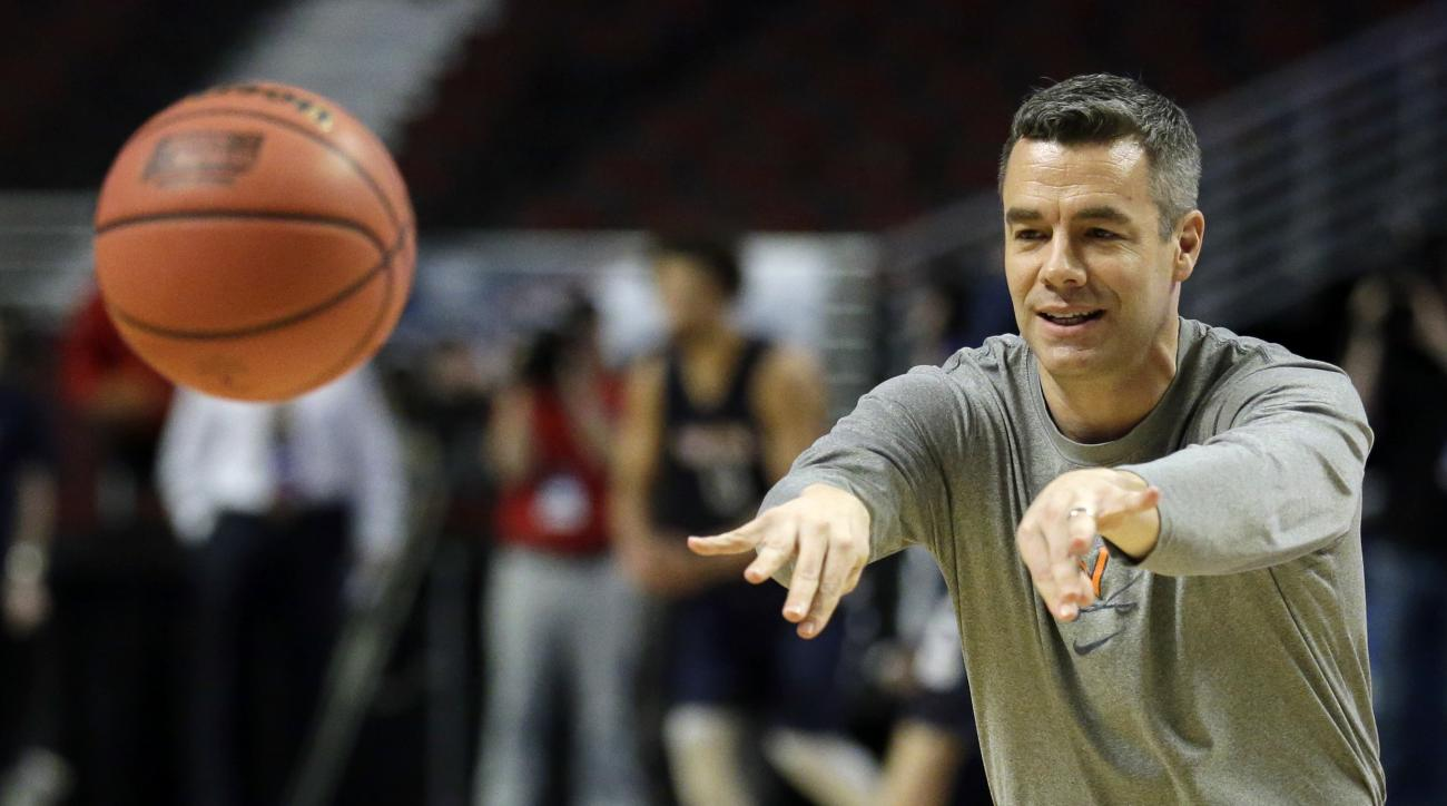 Virginia's head coach Tony Bennett passes the ball during college basketball practice, Thursday, March 24, 2016, in Chicago. Virginia plays against Iowa State in a regional semifinal game in the NCAA Tournament on Friday. (AP Photo/Nam Y. Huh)