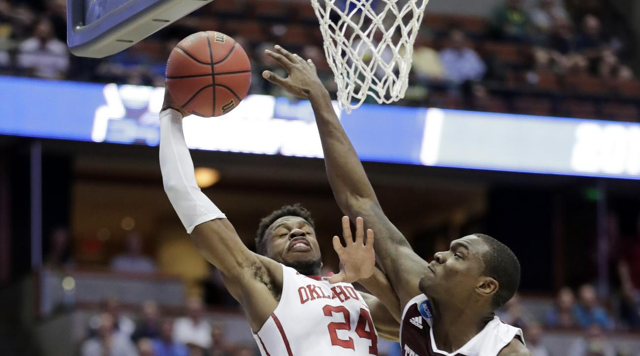 Oklahoma guard Buddy Hield, left, shoots over Texas A&M guard Jalen Jones during the first half of an NCAA college basketball game in the regional semifinals of the NCAA Tournament, Thursday, March 24, 2016, in Anaheim, Calif. (AP Photo/Gregory Bull)