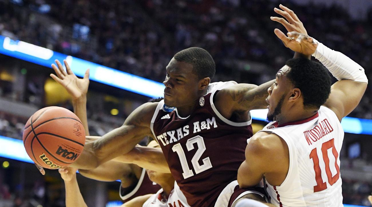 Texas A&M guard Jalen Jones, middle, battles Oklahoma center Jamuni McNeace, left, and guard Jordan Woodard for a rebound during the first half of an NCAA college basketball game in the regional semifinals of the NCAA Tournament, Thursday, March 24, 2016,