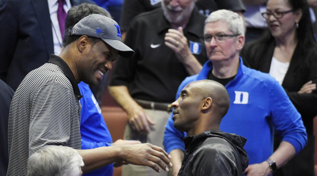 Former NBA player David Robinson, left, talks with Los Angels Laker Kobe Bryant as Tim Cook, CEO of Apple looks on during the second half of an NCAA college basketball game between Oregon and Duke in the regional semifinals of the NCAA Tournament, Thursda
