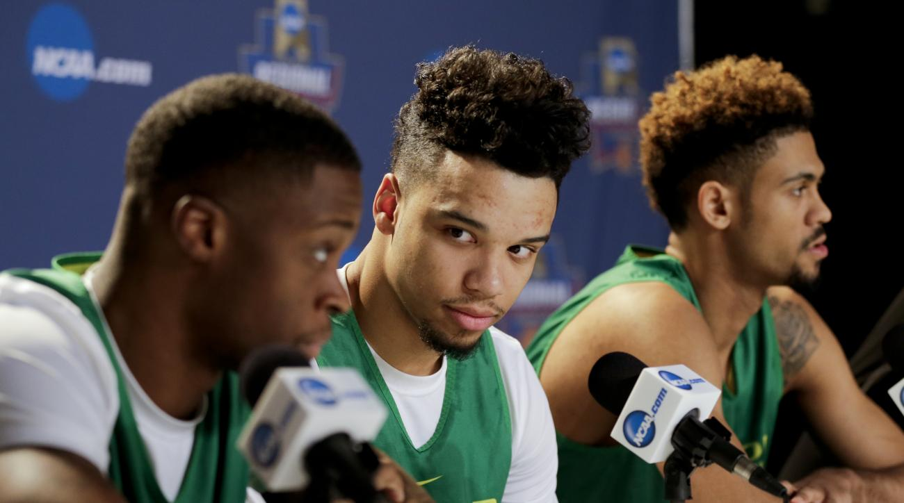 Oregon forward Dillon Brooks, center, looks on between teammate forward Elgin Cook, left, and guard Tyler Dorsey, right, during a news conference before an upcoming regional finals basketball game in the NCAA Tournament Friday, March 25, 2016, in Anaheim,