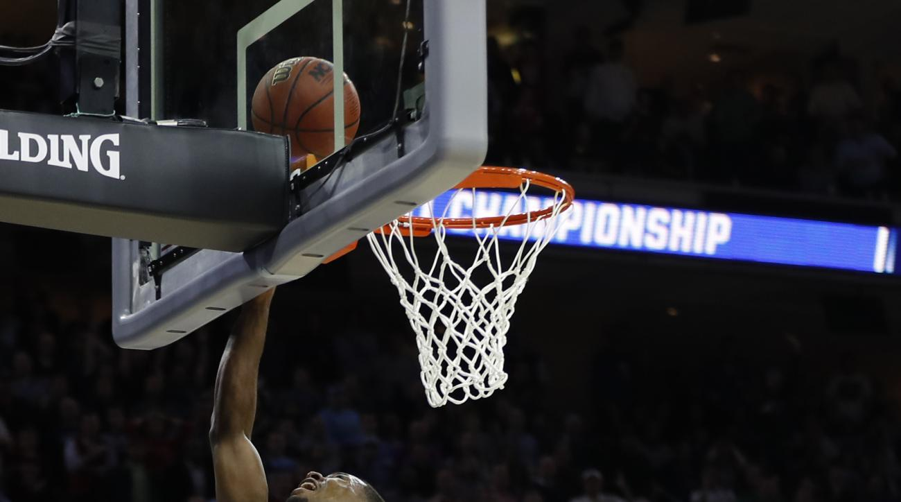 Notre Dame's Demetrius Jackson, left, goes up for a shot past Wisconsin's Bronson Koenig during the second half of an NCAA college basketball game in the regional semifinals of the men's NCAA Tournament, Friday, March 25, 2016, in Philadelphia. Notre Dame
