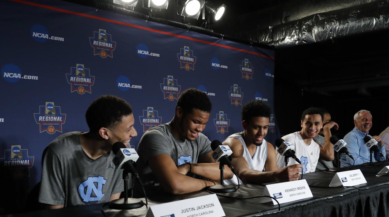 North Carolina's Justin Jackson, from left, Kennedy Meeks, Joel Berry II, Marcus Paige, Brice Johnson and head coach Roy Williams laugh during a college basketball news conference, Saturday, March 26, 2016, in Philadelphia. North Carolina will play Notre