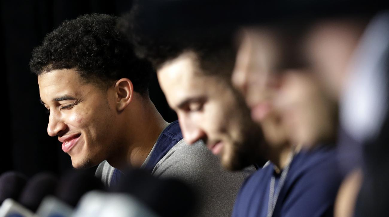 Virginia forward Isaiah Wilkins, left, smiles as he listens to head coach Tony Bennett speak during a news conference, Saturday, March 26, 2016, in Chicago. Virginia plays against Syracuse in a regional final game in the men's NCAA Tournament on Sunday. (