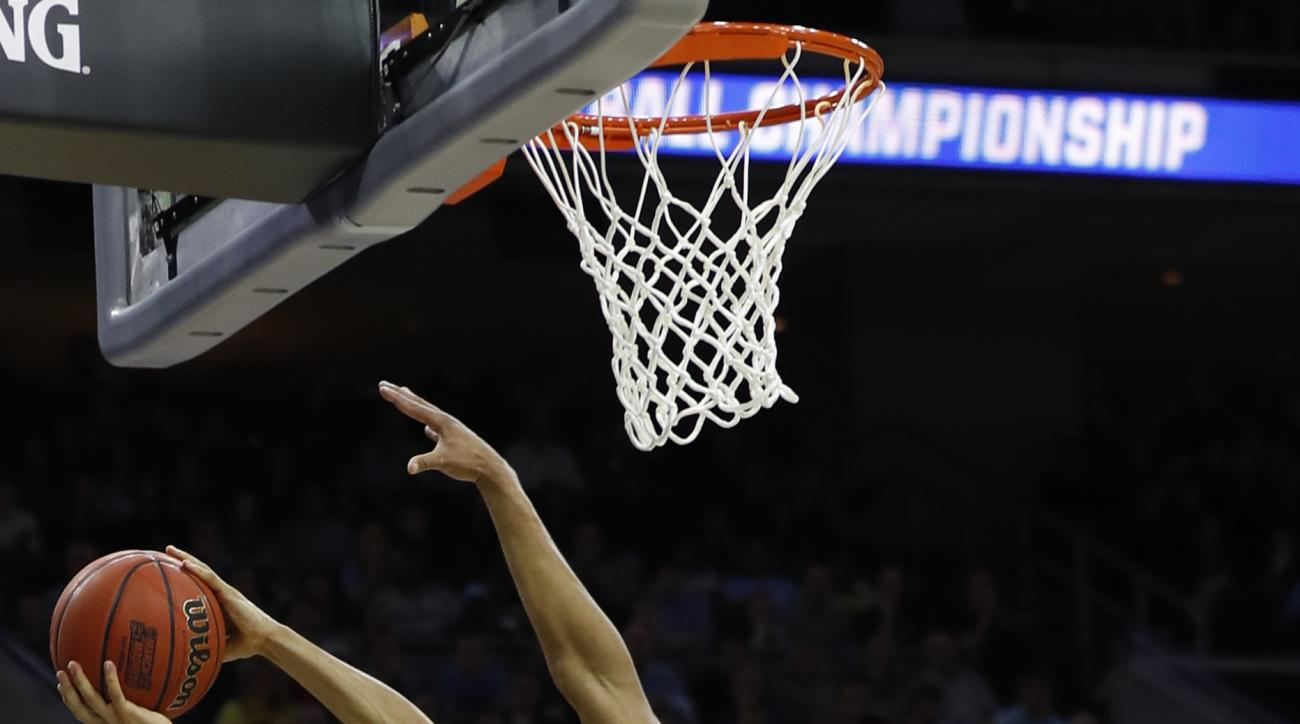 North Carolina's Marcus Paige, left, goes up for a shot against Notre Dame's Bonzie Colson, center, and Zach Auguste during the second half of a regional final men's college basketball game in the NCAA Tournament, Sunday, March 27, 2016, in Philadelphia.