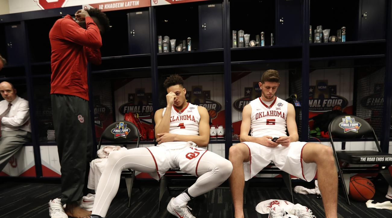 Oklahoma's Jamuni McNeace (4) and Matt Freeman (5) sit in the locker room after the NCAA Final Four tournament college basketball semifinal game against Villanova, Saturday, April 2, 2016, in Houston. Villanova won 95-51. (AP Photo/Eric Gay)