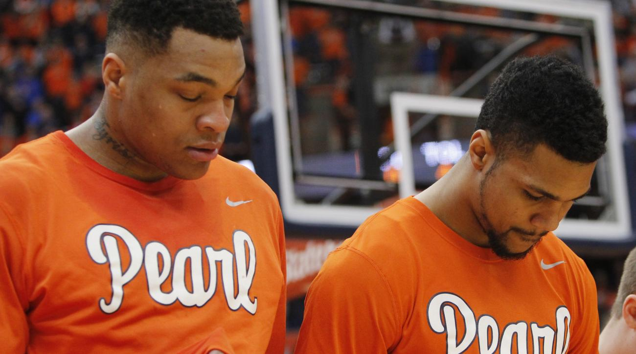 FILE - In this Jan. 30, 2016, file photo, Syracuses Dajuan Coleman, left, and Michael Gbinije, right, wear shirts in support of Syracuse basketball great Dwayne Pearl Washington during the National Anthem before the start of an NCAA college basketball gam
