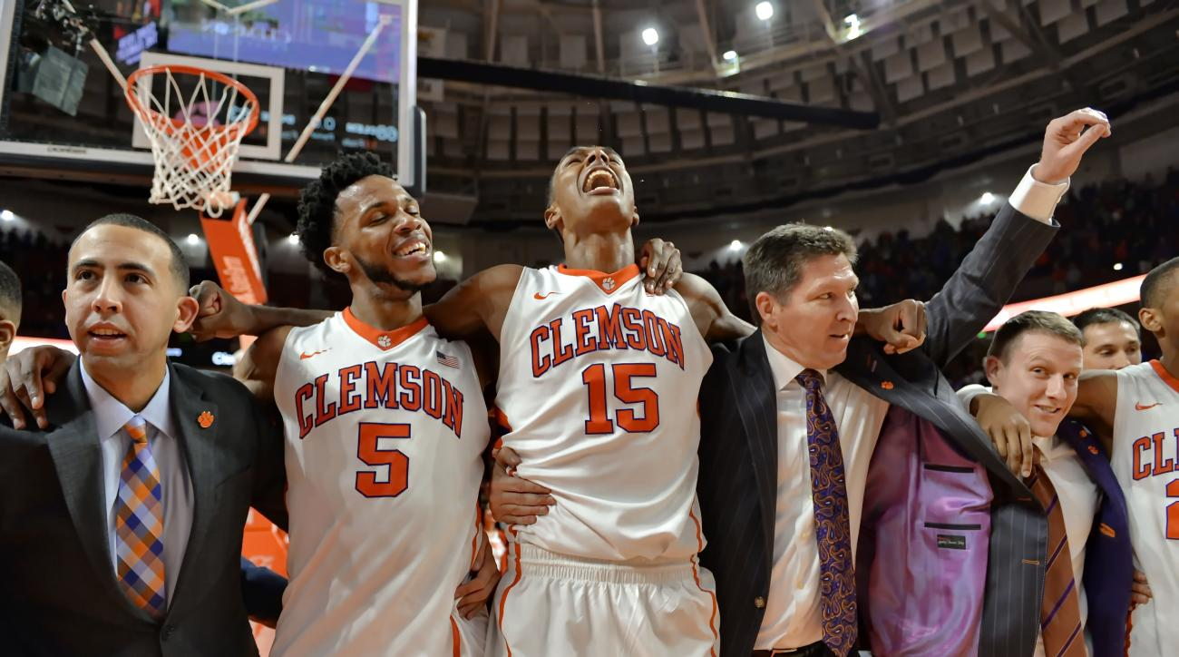 Clemson's Donte Grantham (15) and Jaron Blossomgame (5), with coaches Brad Brownell, right, and Richie Riley, left celebrate after an NCAA college basketball game against Duke on Wednesday, Jan. 13, 2016, in Greenville, S.C. Clemson won 68-63. (AP Photo/R
