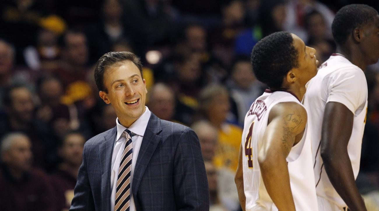 FILE - In this Friday, Dec. 19, 2014 file photo, Minnesota head coach Richard Pitino, left, smiles at his players during the first half of an NCAA college basketball game against Seattle in Minneapolis. With concern expressed by the university president a