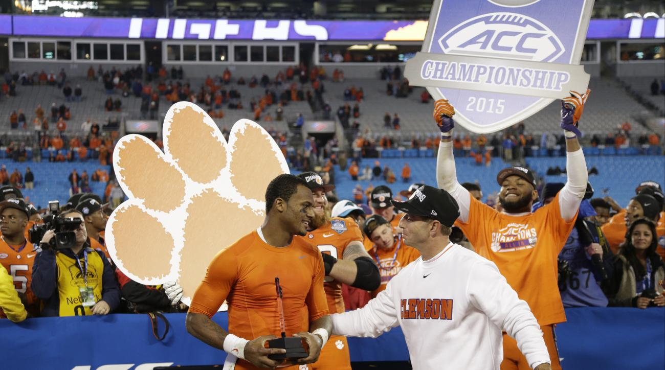 Clemson quarterback Deshaun Watson, left, is congratulated by Clemson head coach Dabo Swinney after Clemson defeated North Carolina in the Atlantic Coast Conference championship NCAA college football game in Charlotte, N.C., Sunday, Dec. 6, 2015. Clemson