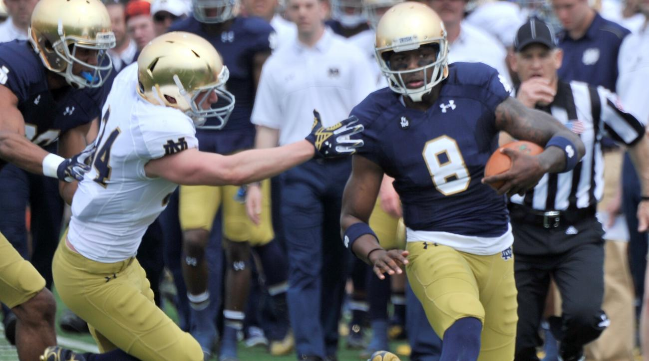 Notre Dame quarterback Malik Zaire (8) avoids being tackled by Jesse Bongiovi (34) during the Blue Gold spring NCAA college football game, Saturday April 18, 2015 in South Bend, Ind. (AP Photo/Joe Raymond)