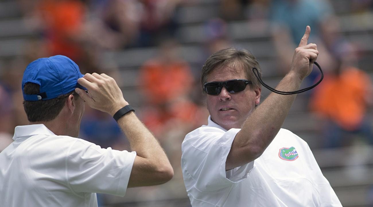 Florida coach Jim McElwain, right, talks with a staff member during the second half of Florida's spring Orange-Blue  college football game in Gainesville, Fla., Saturday, April, 11, 2015. (AP Photo/Phil Sandlin)