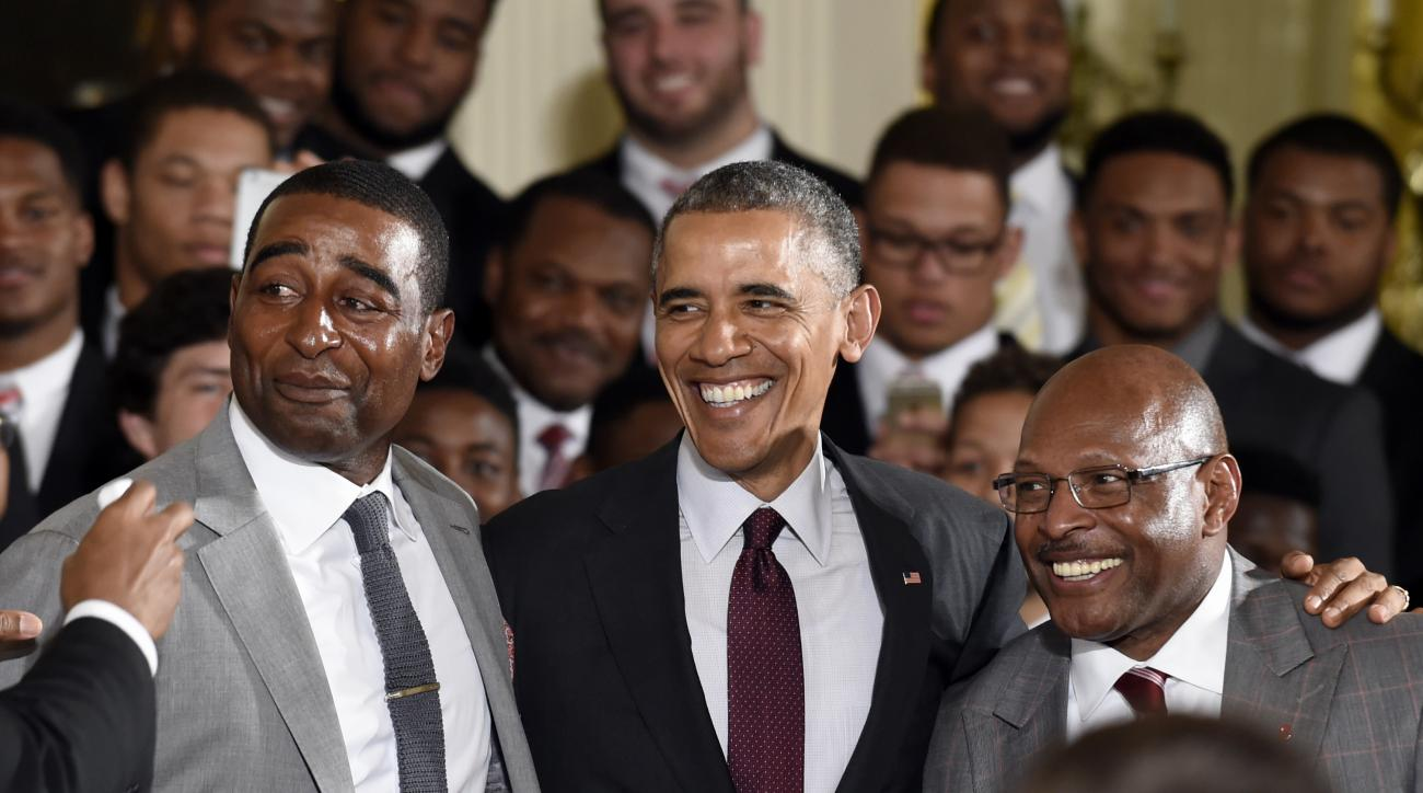 President Barack Obama poses with former Ohio State wide receiver, and pro football hall of famer Cris Carter, left, and former Ohio State running back and two-time Heisman Trophy winner Archie Griffin, right, during a ceremony welcoming the NCAA College