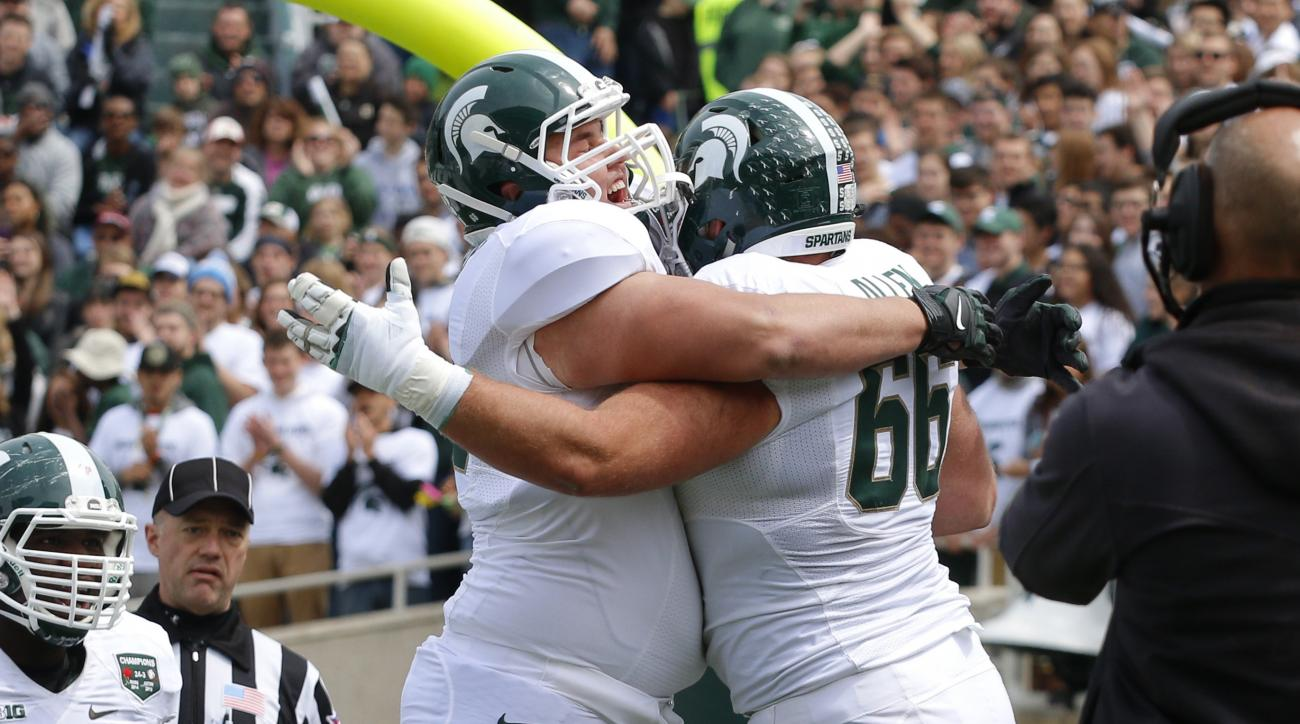 Michigan State White team offensive linemen Jeremy Schram, left, and Jack Allen (66) celebrate Allen's rushing touchdown during the Spartans' spring NCAA college football game, Saturday, April 25, 2015, in East Lansing, Mich. The White team won 9-3. (AP P