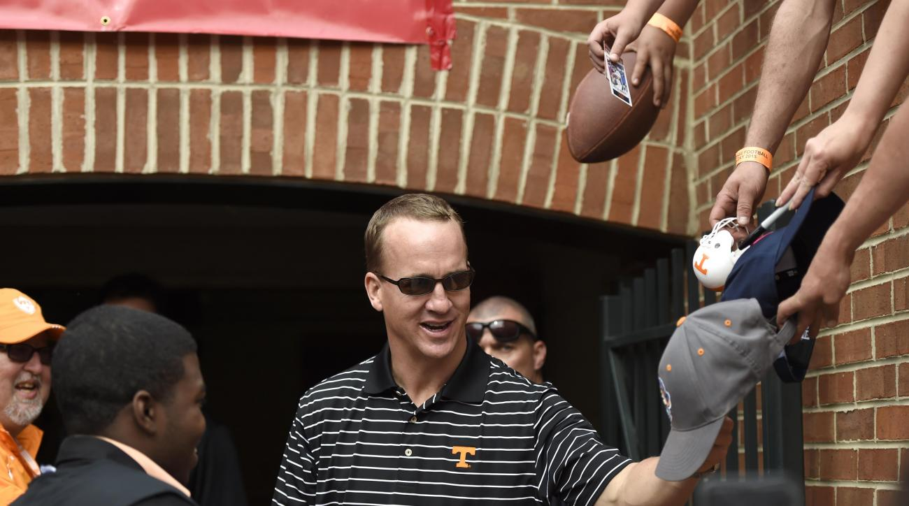 Fans reach to hand memorabilia down to Denver Broncos quarterback Peyton Manning to sign during Tennessee's Orange & White NCAA college football spring game at Neyland Stadium on Saturday, April 25, 2015, in Knoxville, Tenn. (Adam Lau/Knoxville News Senti