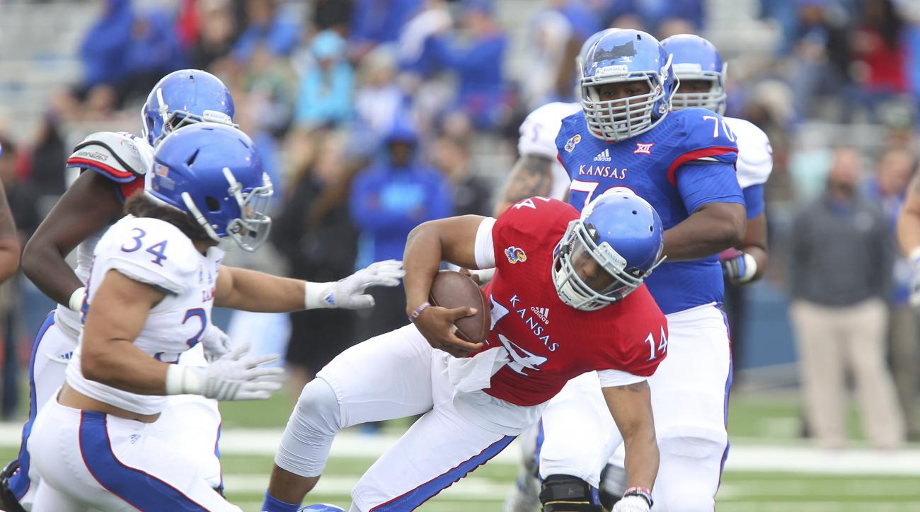 Blue Team quarterback Michael Cummings (14) is taken out at the knees by White Team safety Michael Glatczak (39) on a quarterback run during Kansas University's NCAA college spring football game on Saturday, April 25, 2015, in Lawrence, Kansas. Cummings w
