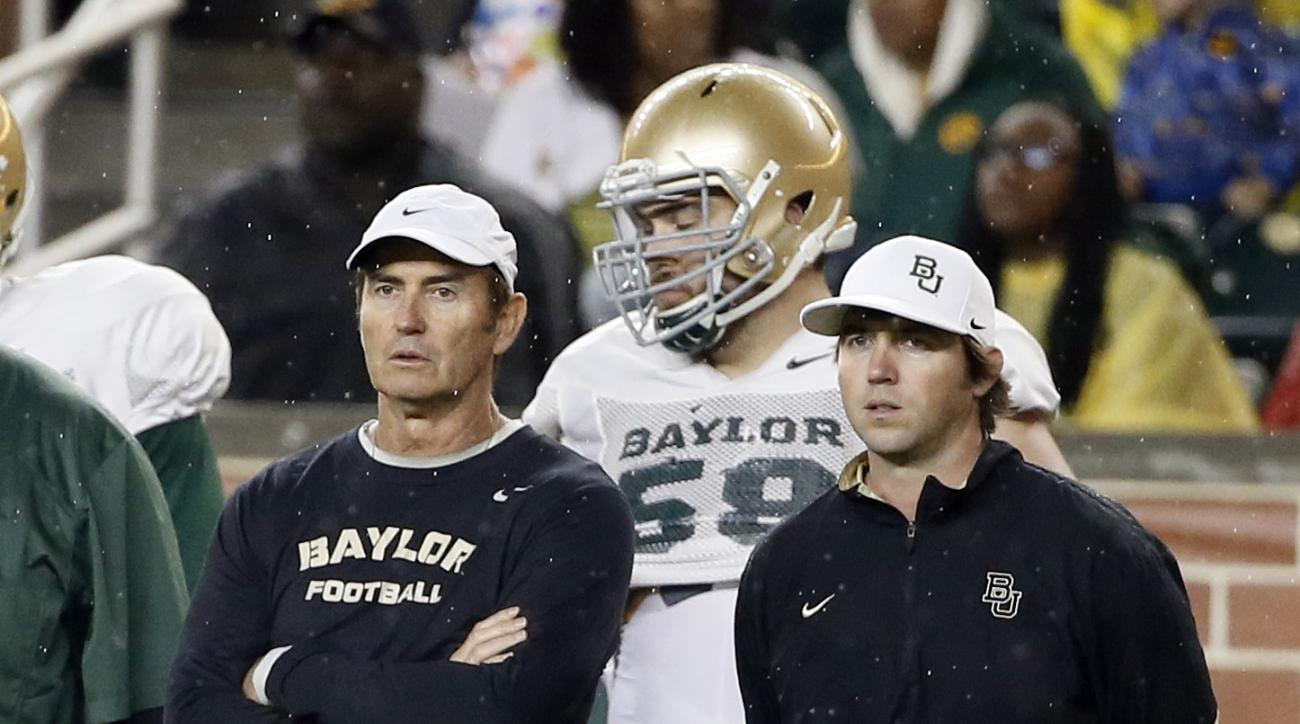FILE - In this March 20, 2015, file photo, Baylor head coach Art Briles, left, and offensive coordinator Kendal Briles, right, watch a play during an NCAA college football intrasquad scrimmage in Waco, Texas. Briles is handing control to his prized posses
